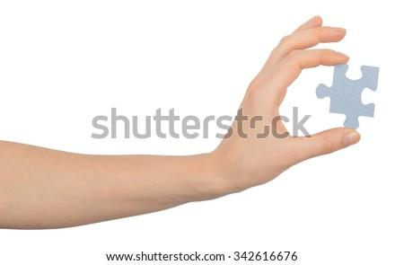 Hand holding puzzle piece on isolated white background - stock photo
