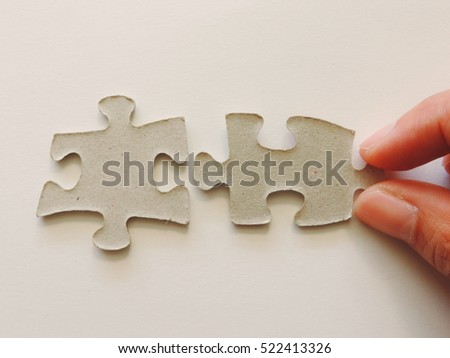 Hand holding puzzle piece  with empty space,close up view.