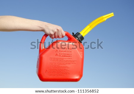 Hand holding red petrol can, isolated with blue sky as background and copy space. - stock photo