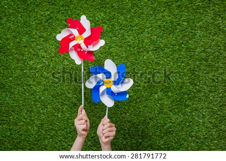 Hand holding red white and blue pinwheels over green grass