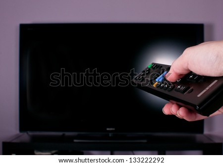 Hand holding remote control for turn off TV - stock photo