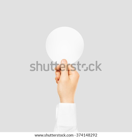 Hand holding round blank white sticker mock up isolated on gray. Sticker mockup holder. Empty paper clue remnder hold in hands. Arm sticking round sticker. - stock photo