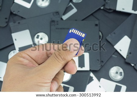 Hand holding SD card with floppy disk background - stock photo