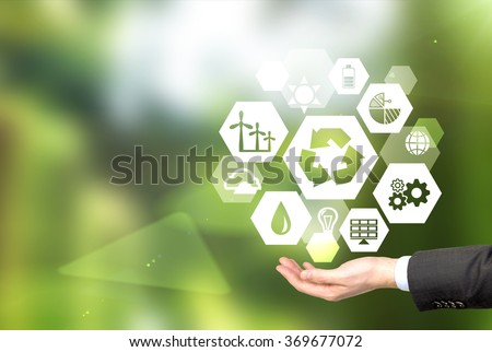 hand holding signs of different green sources of energy in hexahedron shape, a 'reduce, reuse, recycle' sign in the centre. Blurred green background. Concept of clean environment. - stock photo