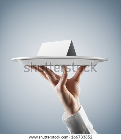 Hand holding silver tray with place card - stock photo