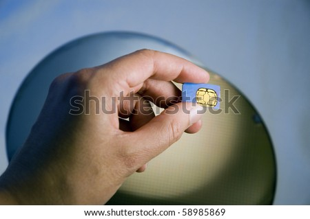 Hand Holding SIM Module Over Silicon Wafers - stock photo