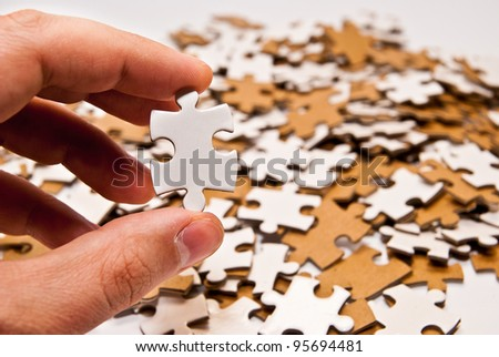 hand holding single puzzle piece - stock photo