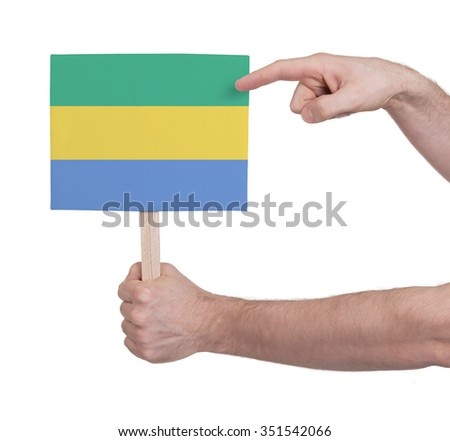Hand holding small card, isolated on white - Flag of Gabon