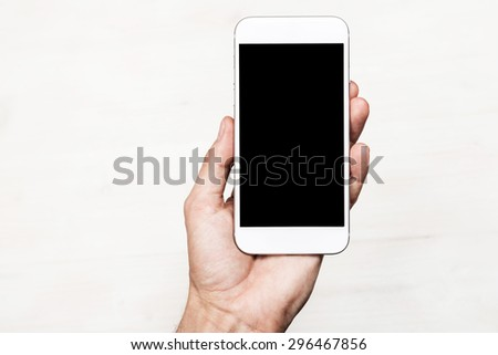 Hand holding smart mobile phone on wooden table and light blurred background - stock photo