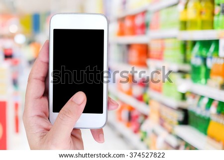 Hand holding smart phone over blur supermarket background, retail business , shopping online and technology concept - stock photo