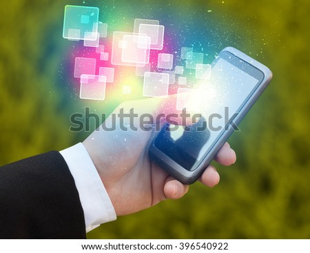Hand holding smart phone with abstract glowing squares concept