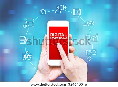 Hand holding smart phone with Digital Advertising word and icon on blue pixel blur background, Digital Marketing concpet. - stock photo
