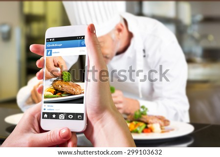 Hand holding smartphone against concentrated male chef garnishing food in kitchen - stock photo