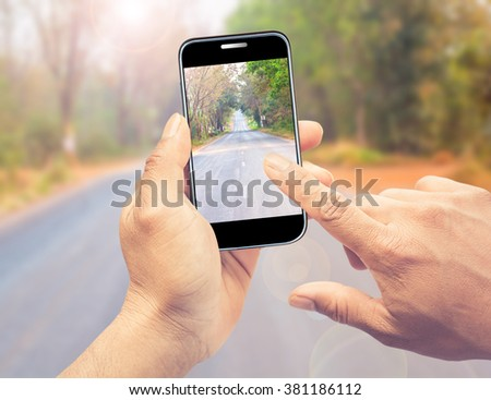 hand holding smartphone and view of road in countryside thailand - stock photo