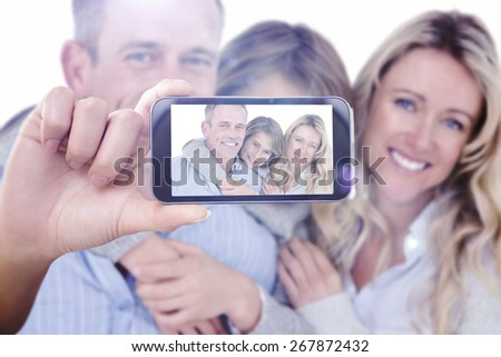 Hand holding smartphone showing against father carrying his son on his back with his wife next to him - stock photo