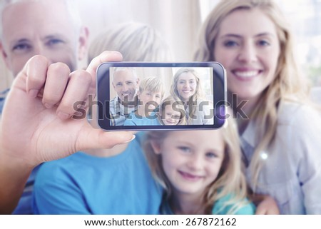 Hand holding smartphone showing against happy family smiling at camera - stock photo