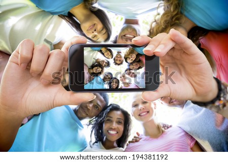 Hand holding smartphone showing friends forming huddle - stock photo