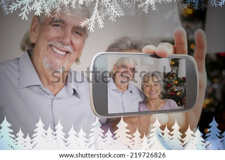 Hand holding smartphone showing photo against frost and fir trees in blue - stock photo