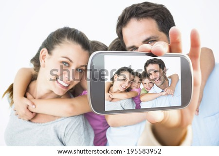 Hand holding smartphone showing smiling young family looking at camera together