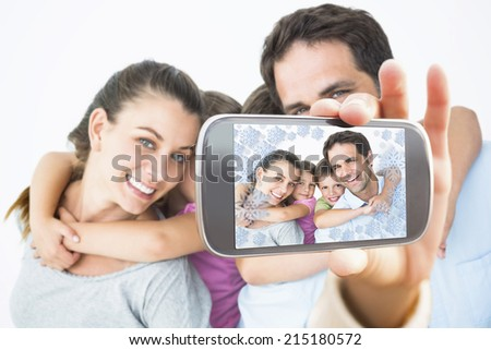 Hand holding smartphone showing smiling young family looking at camera together - stock photo