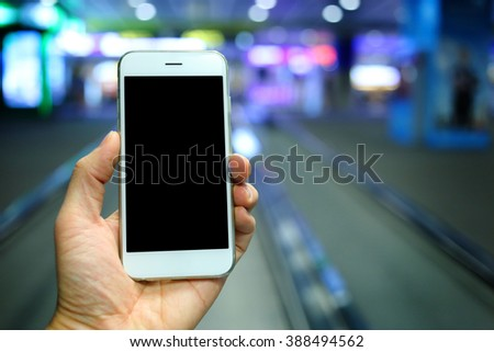 Hand holding smartphone with airport background - stock photo