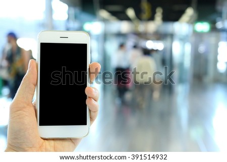 Hand holding smartphone with airport passenger background
