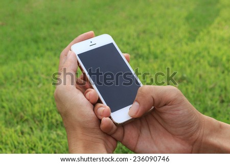 Hand holding smartphone with blank screen - stock photo