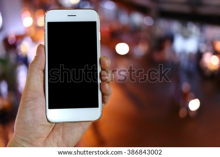 Hand holding smartphone with night light background