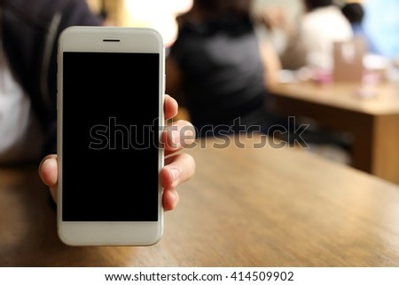 Hand holding smartphone with peoples backgound