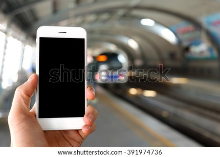 Hand holding smartphone with railway station background - stock photo