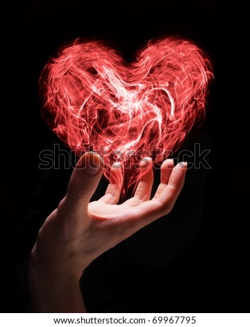 Hand holding smoke heart as a symbol of fragile nature of love or can symbolize someone giving love. - stock photo