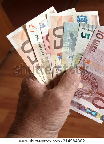 Hand holding some euro banknotes close up - stock photo