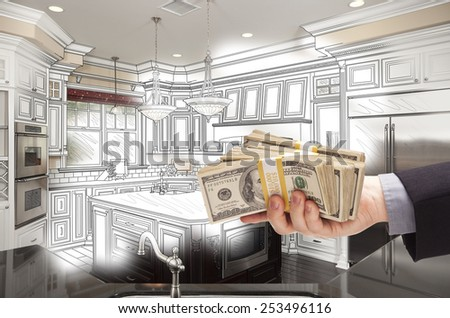 Hand Holding Stacks of Money Over Custom Kitchen Design Drawing and Photo Combination. - stock photo