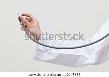 Hand holding stethoscope on clear background - stock photo