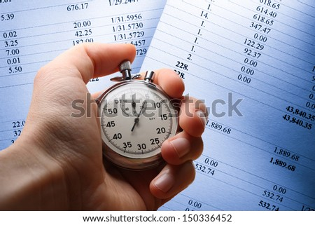 Hand holding stopwatch on budget numbers - stock photo