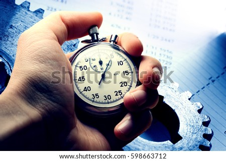 Hand holding stopwatch on budget numbers in closeup