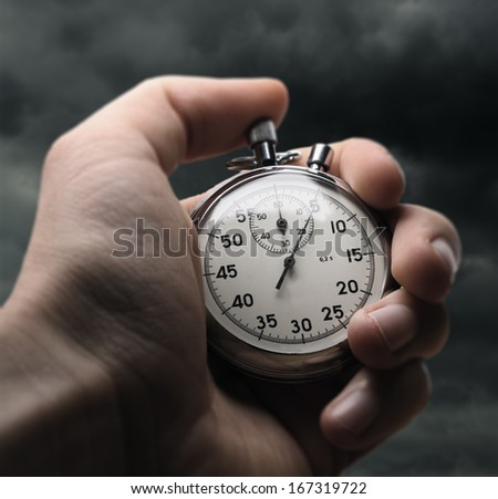 Hand holding stopwatch on stormy sky background - stock photo
