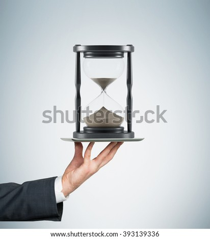 Hand holding tablet horizontally, sand glass in dark wooden carcass on it. Sand running. Concept of time. - stock photo