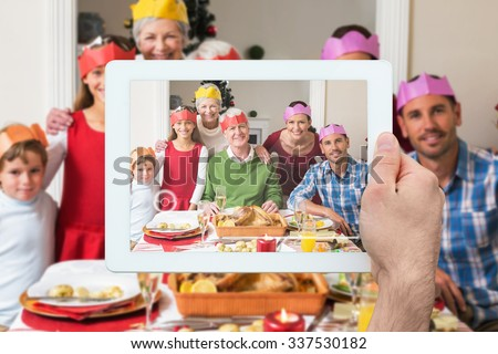 Hand holding tablet pc against happy extended family in party hat at dinner table - stock photo