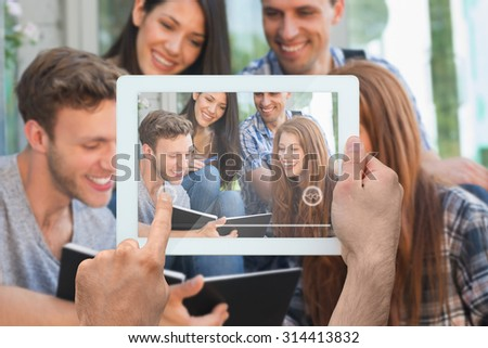 Hand holding tablet pc against happy students looking at book outside on campus - stock photo