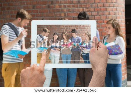 Hand holding tablet pc against happy students standing and reading - stock photo