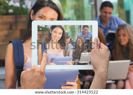 Hand holding tablet pc against pretty student using her tablet pc on campus - stock photo