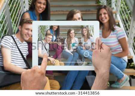 Hand holding tablet pc against smiling students sitting on steps - stock photo