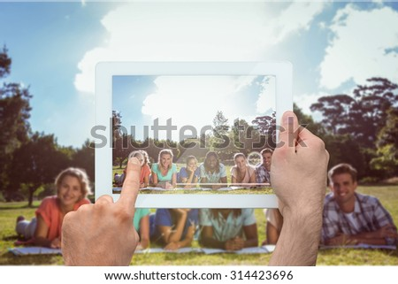 Hand holding tablet pc against students studying outside on campus - stock photo