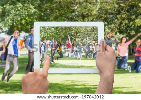Hand holding tablet pc showing college students jumping in the park - stock photo