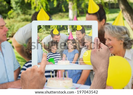 Hand holding tablet pc showing extended family wearing party hats at birthday celebration in park - stock photo