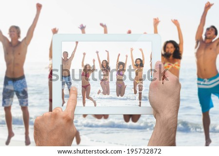 Hand holding tablet pc showing group of friends having fun on the beach - stock photo