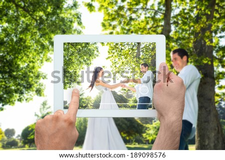 Hand holding tablet pc showing happy couple in the park