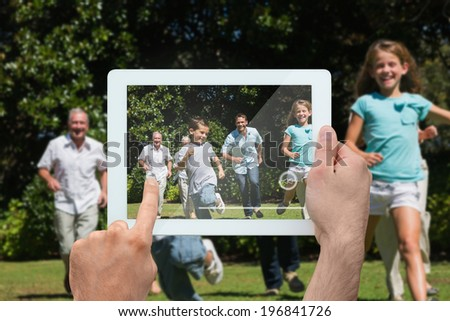 Hand holding tablet pc showing happy multi generation family racing towards camera - stock photo