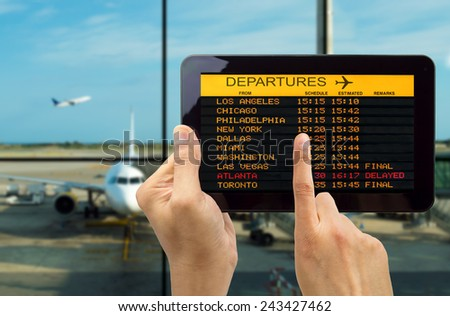 Hand holding tablet with connect wifi on the airport and see departures board - stock photo